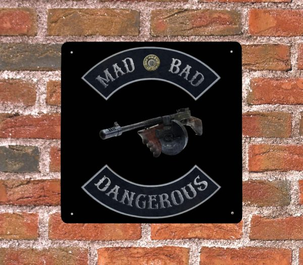 Mad Bad and Dangerous with Tommy Gun Metal Print on Brick wall